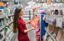 Den unga kvinnliga chauffören köper varningstriangeln i supermarketbilavdelningen Royaltyfri Bild