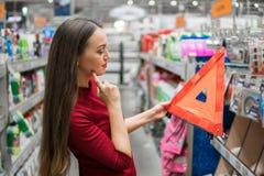 Den unga kvinnliga chauffören köper varningstriangeln i supermarketbilavdelningen Arkivbild