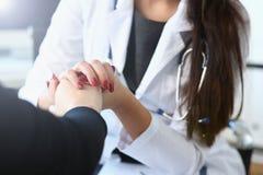 Den unga kvinnliga doktorn rymmer den sjuka patienten vid handen arkivfoton