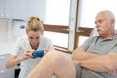 Den unga kvinnliga doktorn som tar fotografiet höga patienter, lägger benen på ryggen Royaltyfria Foton