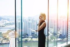 Den unga kvinnliga ekonomen kallar via mobiltelefonen Royaltyfria Foton