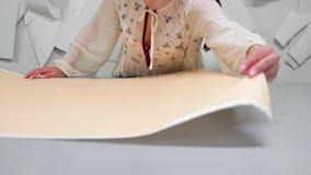 Den unga kvinnliga formgivaren med måttbandet på hennes halsanseende i sömnadstudio och teckning fodrar med krita och regel arkivfilmer