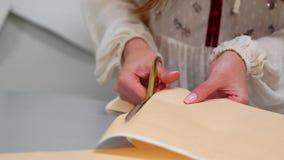 Den unga kvinnliga formgivaren med måttbandet på hennes halsanseende i sömnadstudio och teckning fodrar med krita och regel stock video
