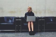 Den unga kvinnliga freelanceren i bra lynne som drömmer om något, medan hållande på knä, öppnar netto-boken, Arkivfoton