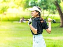 Den unga kvinnliga golfaren värmer upp Royaltyfri Bild