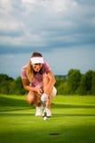 Den unga kvinnliga golfspelaren på kursen som siktar för henne, satte Royaltyfri Bild