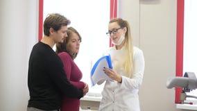 Den unga kvinnliga gynekologen talar med paren stock video