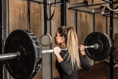 Den unga kvinnliga idrottsman nen utförde squats i idrottshallen royaltyfri foto