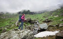 Den unga kvinnliga klättraren som poserar på, vaggar kanten framme av gröna gräs- steniga berg i Rumänien arkivfoto