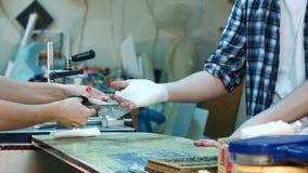 Den unga kvinnliga kollegan som förbinder försiktigt arbetaren, sårade handen efter olycka i seminarium Royaltyfri Fotografi
