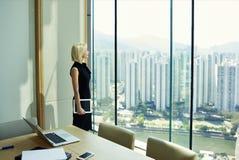 Den unga kvinnliga kompetenta finansiären tänker om något under avbrott på arbetsdagen royaltyfri bild