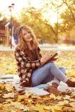 Den unga kvinnliga konstnärteckningen skissar, medan sitta Royaltyfri Foto
