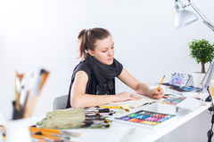 Den unga kvinnliga konstnärteckningen skissar genom att använda sketchbooken med blyertspennan på hennes arbetsplats i studio Stå Royaltyfri Bild
