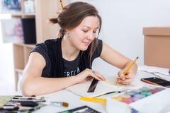 Den unga kvinnliga konstnärteckningen skissar genom att använda sketchbooken med blyertspennan på hennes arbetsplats i studio Stå Arkivfoto