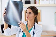 Den unga kvinnliga medicinska doktorn eller allmäntjänstgörande läkaren som ser lungor, x-ray ima Royaltyfri Foto