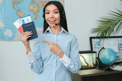 Den unga kvinnliga resebyråmankonsulenten turnerar in byråvisningdokument Royaltyfri Foto