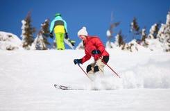 Den unga kvinnliga skieren på ett snöig sluttar Royaltyfria Bilder
