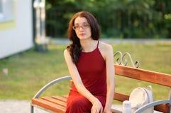 Den unga kvinnliga studenten i Eyesglasses sitter på bänken under Sunny Day i sommaren Royaltyfri Foto