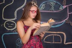 Den unga kvinnliga studenten i röd klänning och exponeringsglas läser boken fotografering för bildbyråer