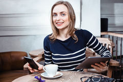 Den unga kvinnliga studenten pratar på den digitala minnestavlan med vännen, medan sitta i kafét, den attraktiva kvinnan som anvä Royaltyfri Foto