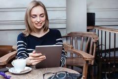 Den unga kvinnliga studenten pratar på den digitala minnestavlan med vännen, medan sitta i kafét som smilling attraktivt använda  Royaltyfri Bild