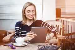 Den unga kvinnliga studenten pratar på den digitala minnestavlan med vännen, medan sitta i kafét som smilling attraktivt använda  Arkivfoto