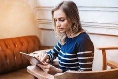 Den unga kvinnliga studenten pratar på minnestavlablocket med vännen, medan sitta i det moderna kafét, ursnyggt Caucasian använda Arkivfoton