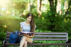 Den unga kvinnliga studenten som sitter på bänk, och läseboken parkerar in royaltyfri foto