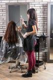 Den unga kvinnliga stylisten rymmer i handlås av hår av den unga kvinnan Arkivbilder