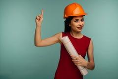 Den unga kvinnliga teknikern i orange hjälm med teckningspunkter fingrar upp isolerat på blå bakgrund royaltyfri bild