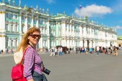 Den unga kvinnliga turisten passerar vinterslotten i helgonet Petersbur Arkivbilder