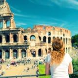 Den unga kvinnliga turisten ser Colosseumen i Rome Arkivbild