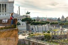 Den unga kvinnliga turisten ser forumet av Trajan och piazza Royaltyfri Foto