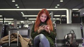 Den unga kvinnlign använder telefonen i flygplatsterminal