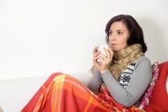 Den unga kvinnlign fångade förkylning som dricker te som känner sig dåligt Arkivfoton