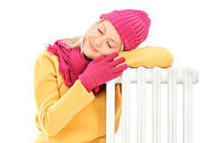 Den unga kvinnlign i vinter beklär att vila på ett element arkivbild