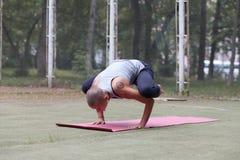 Den unga kvinnlign i yogakran poserar utomhus- royaltyfria foton