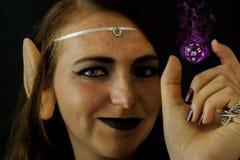 Den unga kvinnlign klädde som en älva med ett polyhedral dör Arkivbild