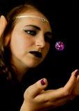Den unga kvinnlign klädde som en älva med ett polyhedral dör Arkivbilder