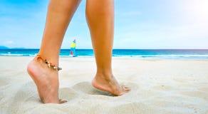 Den unga kvinnlign lägger benen på ryggen ett armband på den sandiga stranden Royaltyfri Bild