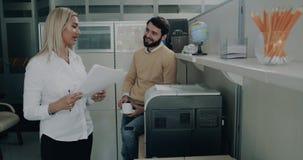 Den unga kvinnlign med en ung man har en stor konversation i kontoret till att få skriva ut någon legitimationshandlingar lager videofilmer