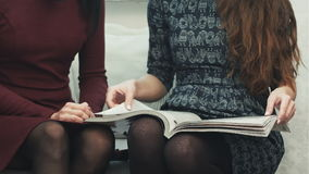 Den unga kvinnlign räcker bläddring till och med ett sammanträde för modetidskrift på en soffa stock video