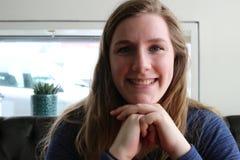 Den unga kvinnlign som åldras 20 till 25, sitter i ett kafé Blont hår och blåa ögon, massor av kopieringsutrymme Fotografering för Bildbyråer