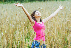 Den unga kvinnlign står i skördfält Arkivfoto
