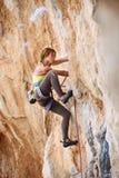 Den unga kvinnlign vaggar klättraren en framsida av en klippa Arkivfoto