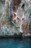 Den unga kvinnlign vaggar klättraren på framsida av klippan Fotografering för Bildbyråer