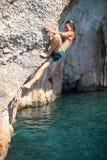 Den unga kvinnlign vaggar klättraren på klippan Arkivbild