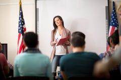 Den unga läraren ger föreläsning till studenter Arkivbild