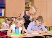 Den unga läraren hjälper studenter av grundskola för barn mellan 5 och 11 år i examen Royaltyfri Bild
