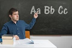 Den unga läraren undervisar abc:et på grundskolan Märker skriftligt på svart tavla Royaltyfria Foton